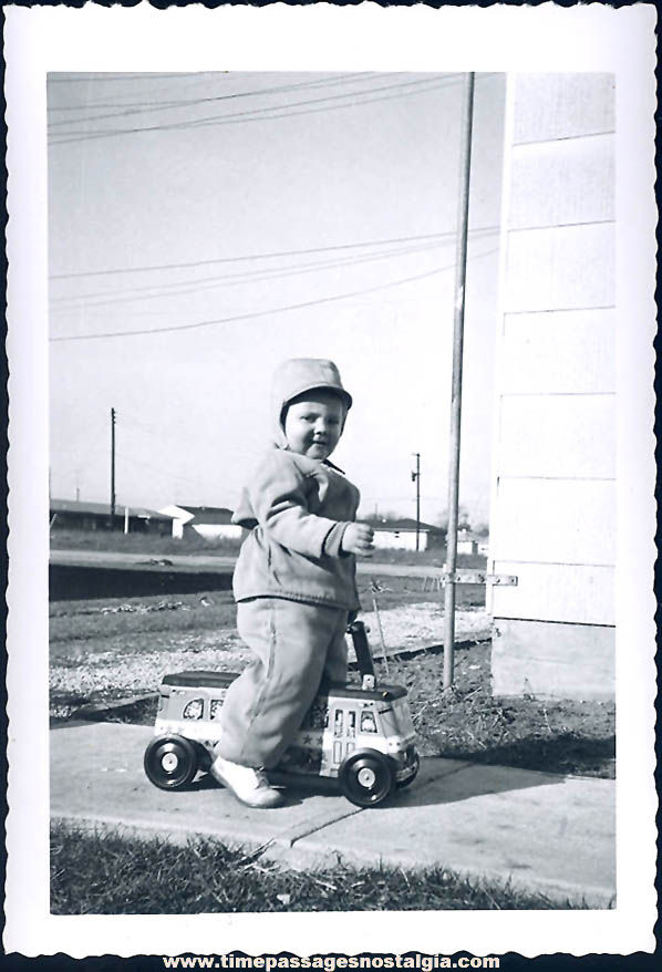 Old Black & White Photograph of Child on an Old Ride On Toy Bus